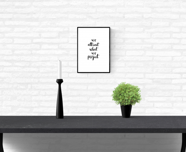 """Wall quote print with the words, """"we attract what we project"""", framed and mounted on a home's interior white brick wall"""