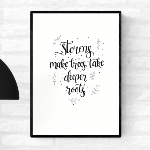 """Framed black and white art illustration with the words, """"Storms make trees take deeper roots"""", surrounded by leaves"""