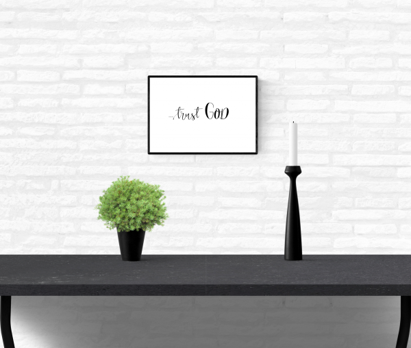 """Interior home white brick wall with a framed and mounted wall quote typography print with the words, """"Trust God"""""""