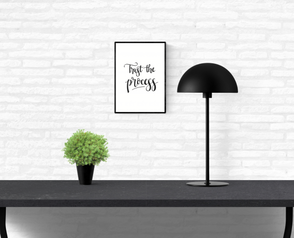 "A white, brick home dining room wall with a hung, framed quote print with the words, ""Trust the process"""