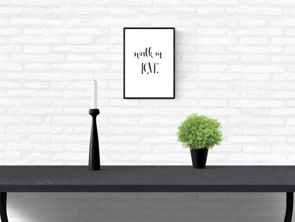 "Quote wall print of Ephesians 5:2 scripture from the New Testament of Holy Bible with the words ""Walk in love"" written mounted on an interior white brick home wall above a table"