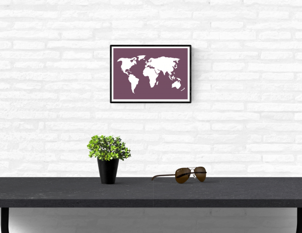 Framed and mounted wall art print of a world map on a home's interior white brick wall